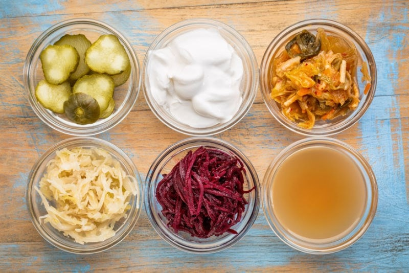 Six little bowls of various fermented foods.