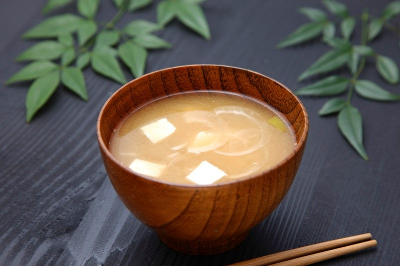 Wooden bowl full of miso soup.