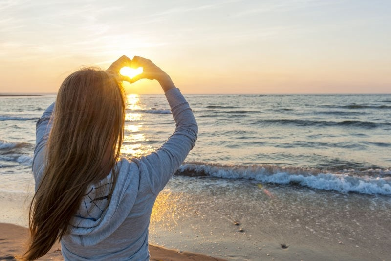 Woman on beach making a heart shape with her hands