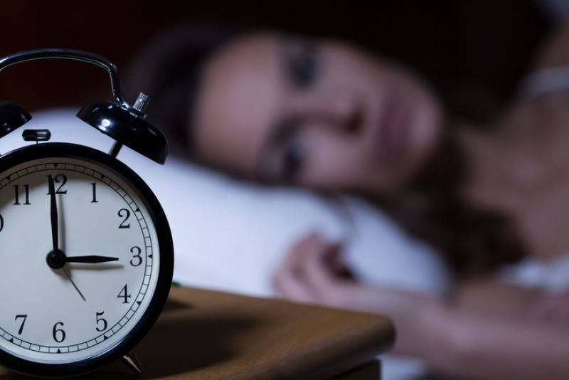 woman lying beside alarm clock